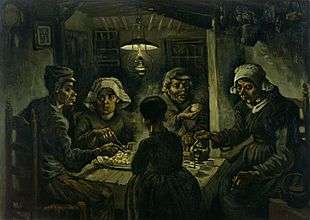 A group of five sit around a small wooden table with a large platter of food, while one person pours drinks from a kettle in a dark room with an overhead lantern.