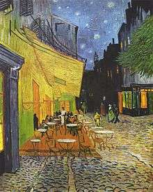 The outdoor terrace of a cafe with several tables filled with patrons. People are walking along the street under a starry sky.